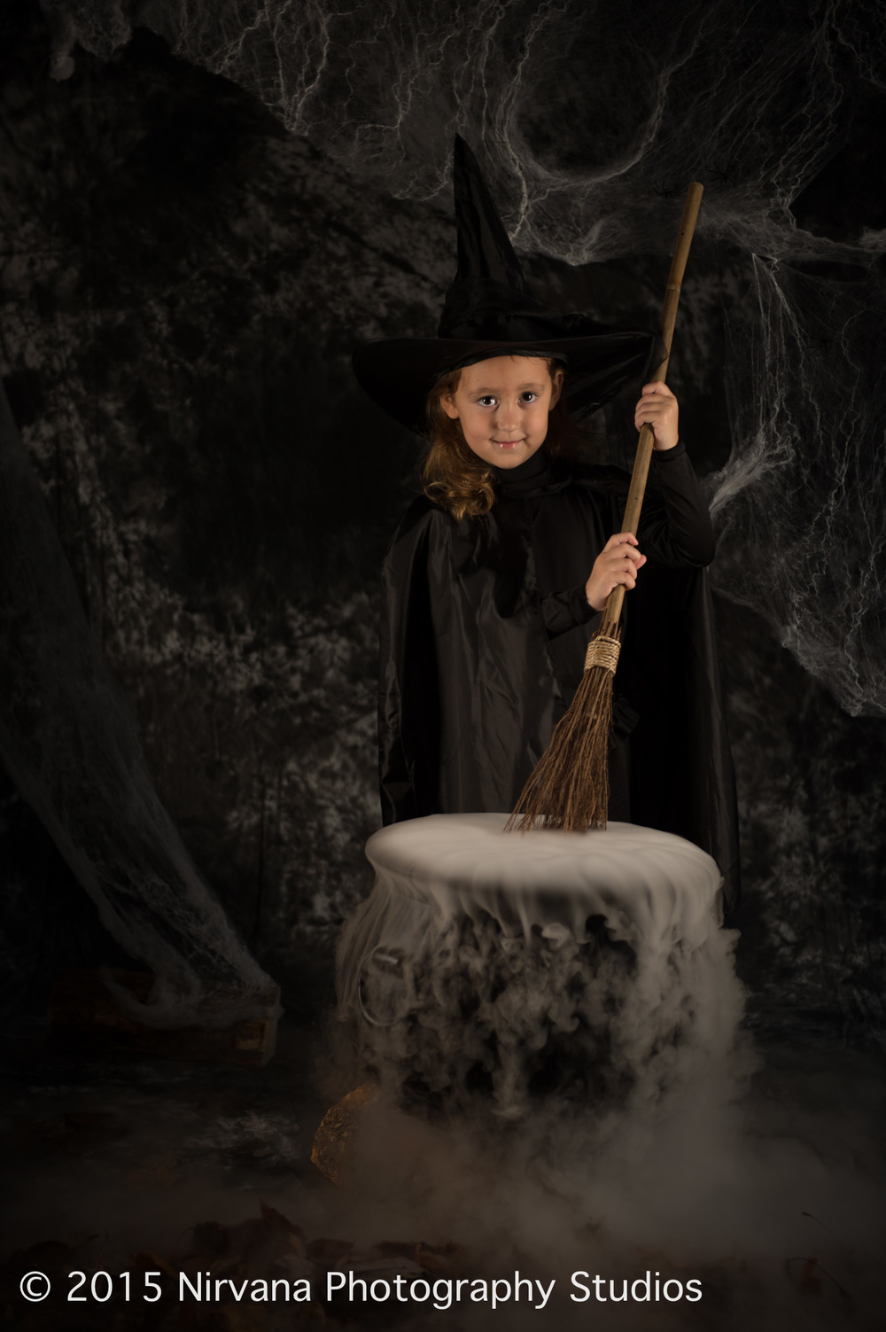Little witch holding a broomstick