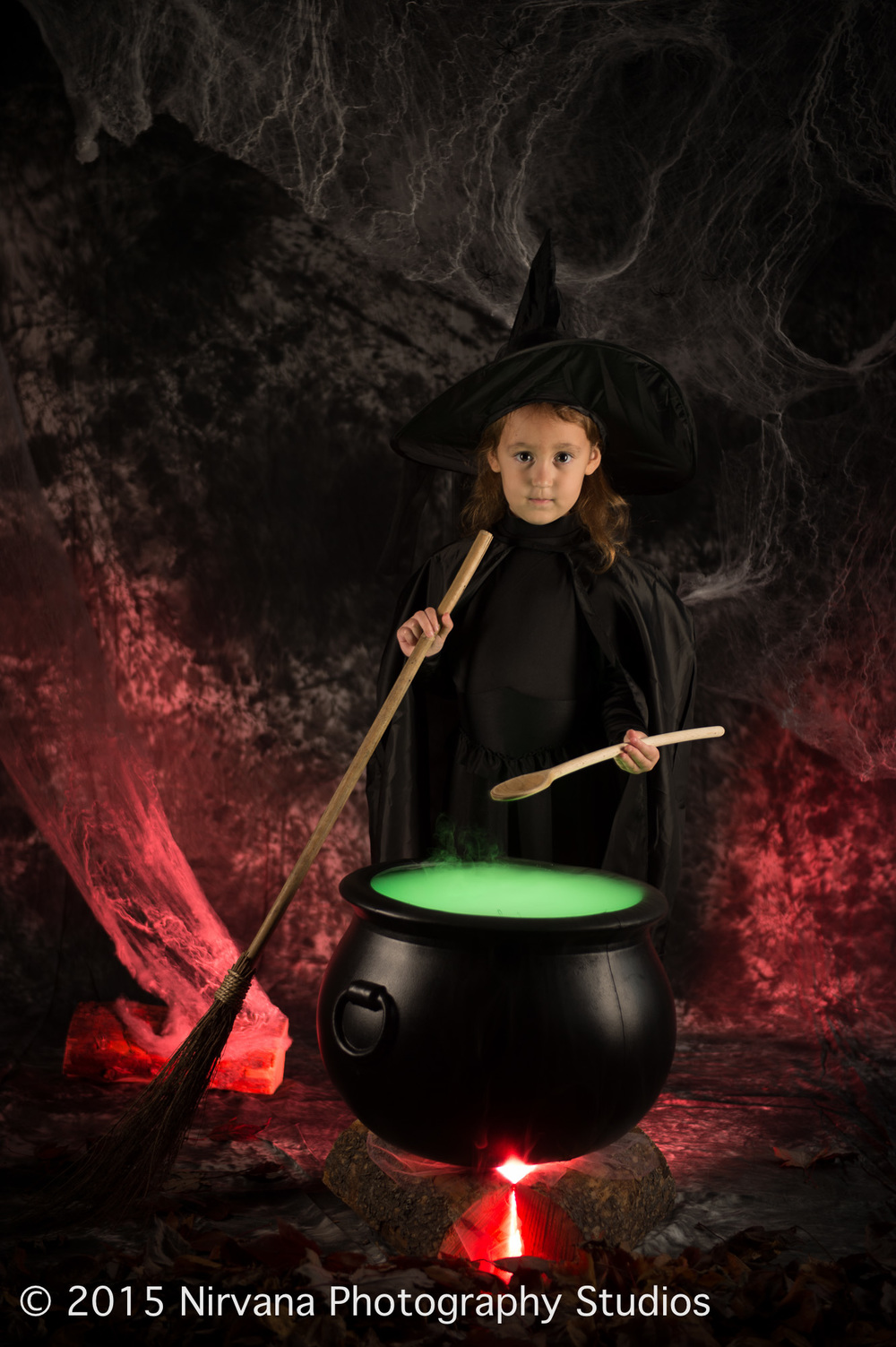 Little witch in front of a big pot