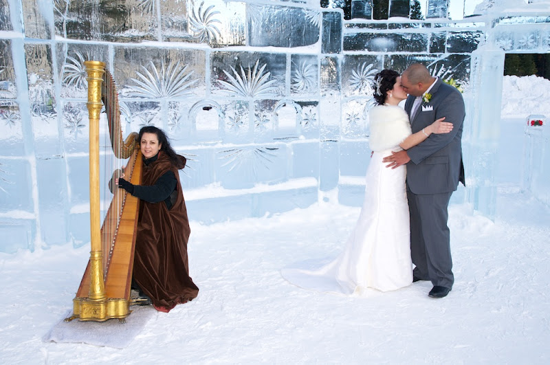 Bride and Groom Kissing in the snow with a woman playing harp