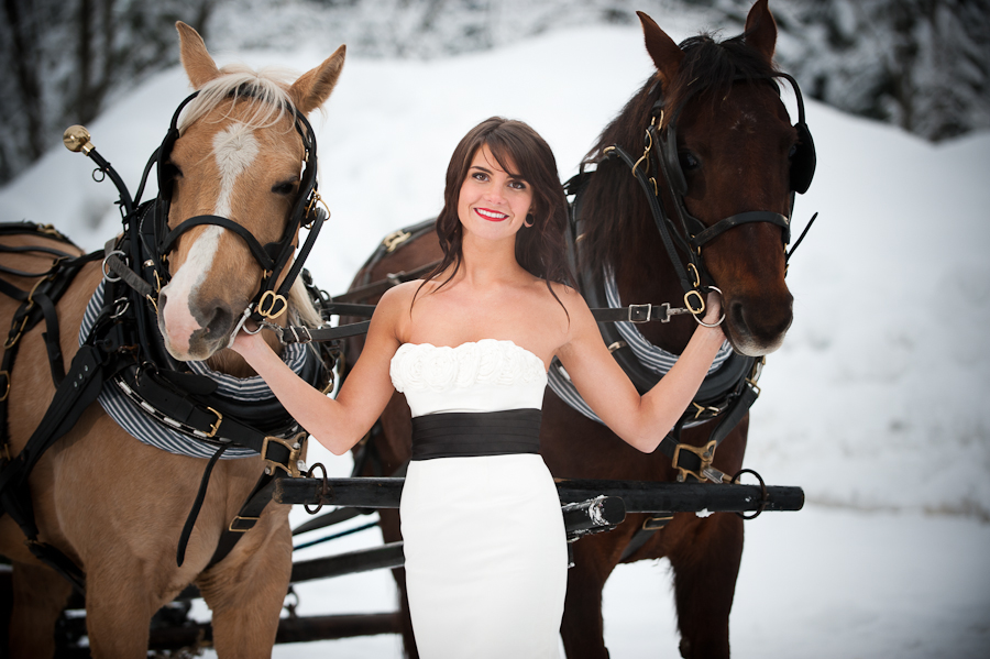 Bride holding two horses in the snow