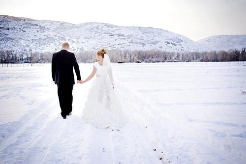 Winter wedding bride and groom holding hands while walking in the snow