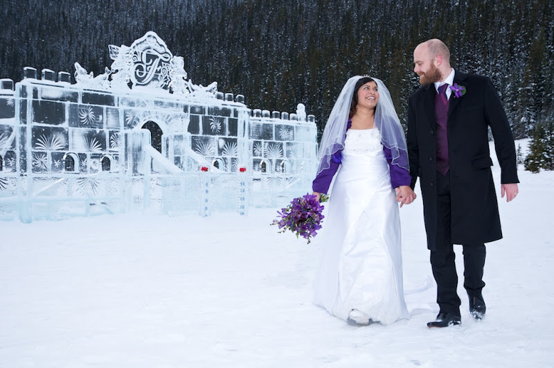 bride and groom holding hands while walking in the snow